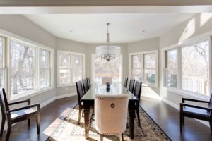 Large sun-filled dining room surrounded by windows